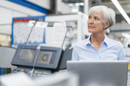 Senior businesswoman with laptop in a factory looking around - DIGF05775