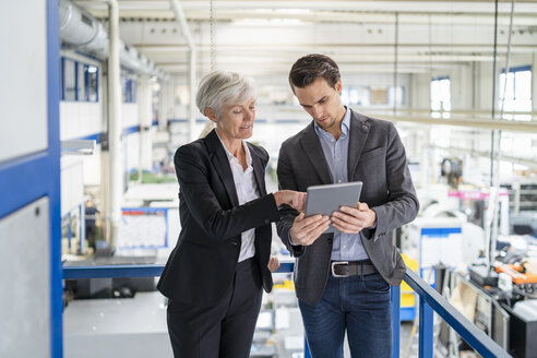 Businessman and senior businesswoman with tablet talking in a factory - DIGF05802