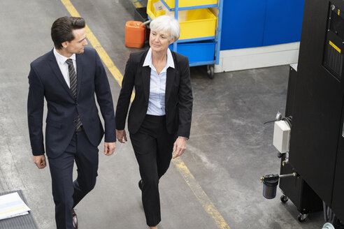 Businessman and senior businesswoman walking in a factory - DIGF05817