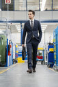 Businessman walking in a factory - DIGF05820