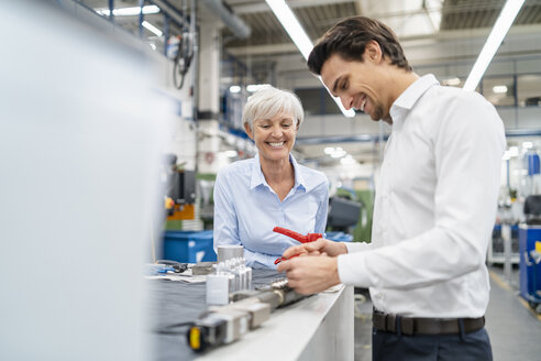 Happy businessman and senior businesswoman examining workpiece in a factory - DIGF05829