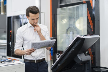 Businessman reading manual at a machine in a factory - DIGF05835