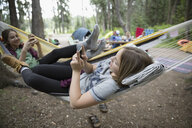 Teenage girl friends relaxing, texting with cell phones in hammocks at outdoor school campsite - HEROF21806