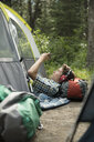 Teenage boy relaxing, camping and listening to music with headphones and mp3 player in tent - HEROF21824