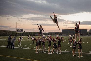 Teenage girl high school cheerleading team cheering and jumping on sideline of game on football field - HEROF21860