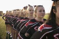 Teenage girl high school cheerleading team poised, standing in a row - HEROF21866