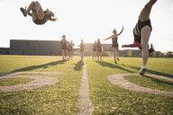 Teenage girl high school cheerleading team walking and flipping on sunny football field - HEROF21869