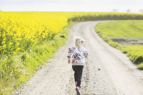 Rear view of girl running on dirt road at oilseed rape field - ASTF02816