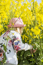 Rear view of girl at rapeseed field - ASTF02819