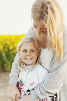 Portrait of happy girl standing with loving mother at rapeseed field - ASTF02825