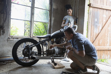 Couple drinking beer and fixing motorcycle in garage - HEROF21908