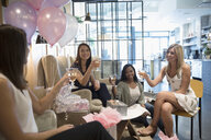 Bride-to-be and bridesmaid friends drinking champagne and getting pedicures at bridal shower in nail salon - HEROF21995