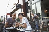 Couple drinking wine and using cell phone at sidewalk cafe - HEROF21998
