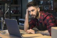 Serious, focused motorcycle shop owner working at laptop - HEROF22052