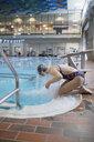Teenage girl preparing, splashing water at swimming pool - HEROF22088