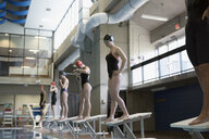 Young women swimmers ready, standing on starting platforms in swimming pool - HEROF22094