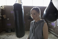 Serious female boxer next to punching bags in gym - HEROF22127
