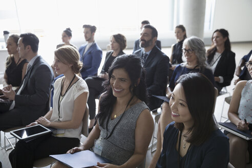Smiling businesswomen listening in conference audience - HEROF22175