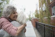 Smiling senior women hugging on urban sidewalk - HEROF22184
