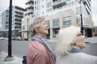 Senior women looking up at urban buildings - HEROF22190