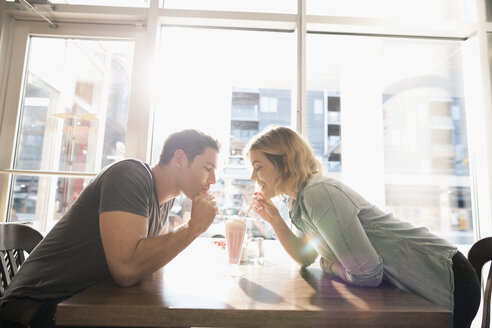 Young couple sharing milkshake at sunny diner table - HEROF22229