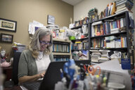 Smiling female college professor working at laptop in messy office - HEROF22247