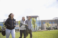 Smiling college students walking in sunny lawn on college campus - HEROF22250
