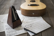 Still life of metronome, sheet music and guitar - HEROF22256