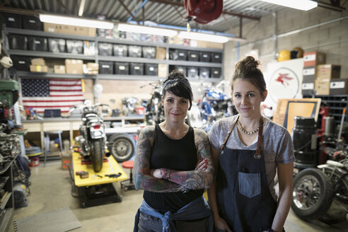 Portrait confident, smiling female motorcycle mechanics in auto repair shop - HEROF22298