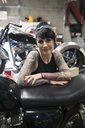 Portrait confident female motorcycle mechanic with tattoos in auto repair shop - HEROF22301