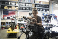 Portrait confident female motorcycle mechanic on motorcycle in auto repair shop - HEROF22304