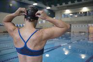 Rear view female swimmer adjusting swimming cap at swimming pool - HEROF22349