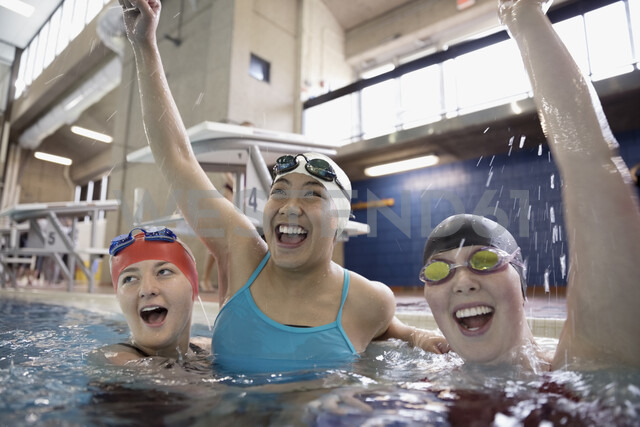 Portrait smiling female swimmers cheering and celebrating in swimming pool - HEROF22352 - Hero Images/Westend61