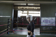 Portrait tough female boxer looking away in boxing ring - HEROF22379
