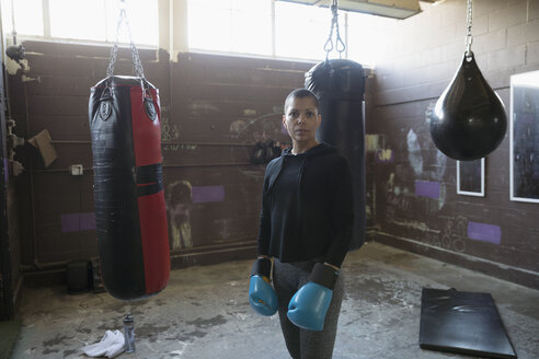 Portrait confident, tough female boxer in boxing gloves near punching bags in gritty gym - HEROF22382