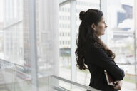 Pensive businesswoman looking out office window - HEROF22415