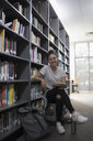Portrait confident, smiling female college student leaning on bookshelf in library - HEROF22448