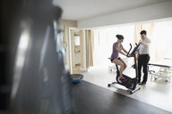 Male physiotherapist guiding female client exercising on exercise bicycle in clinic gym - HEROF22526
