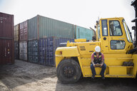 Male worker with clipboard sitting at forklift in sunny industrial container yard - HEROF22583