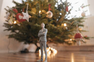 Businessman figurine standing next to a Christmas tree at home - FLAF00152
