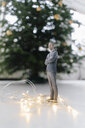 Businessman figurine standing next to a Christmas tree at home - FLAF00158