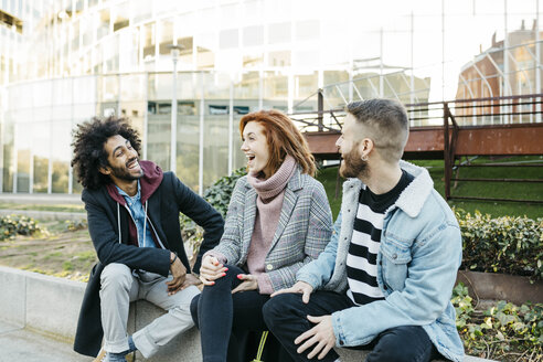 Spain, Barcelona. Three happy friends talking while sitting on a street bench - JRFF02625