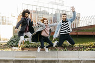 Three happy friends jumping in the city - JRFF02628