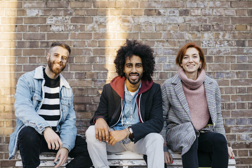 Portrait of three happy friends sitting on a bench in front of a brick wall - JRFF02634