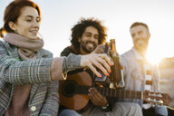 Three happy friends with guitar toasting beer bottles at sunset - JRFF02658