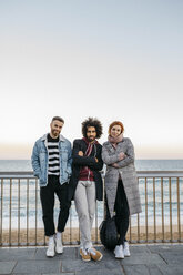 Portrait of three friends standing at the sea - JRFF02664