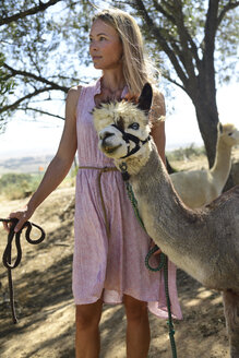 Portrait of woman with leashed alpaca in nature - ECPF00491