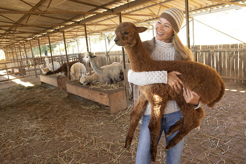 Portrait of smiling mature woman carrying young alpaca in her arms - ECPF00503