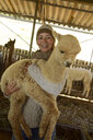 Portrait of smiling mature woman carrying young alpaca in her arms - ECPF00506