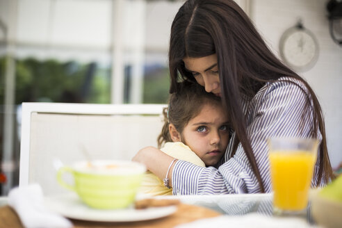 Mother embracing her sad daughter during breakfast in Madrid, Spain. - ABZF02227